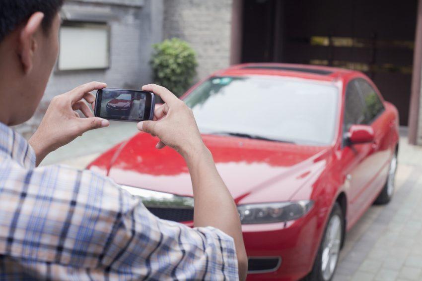 Man taking photo of car using phone